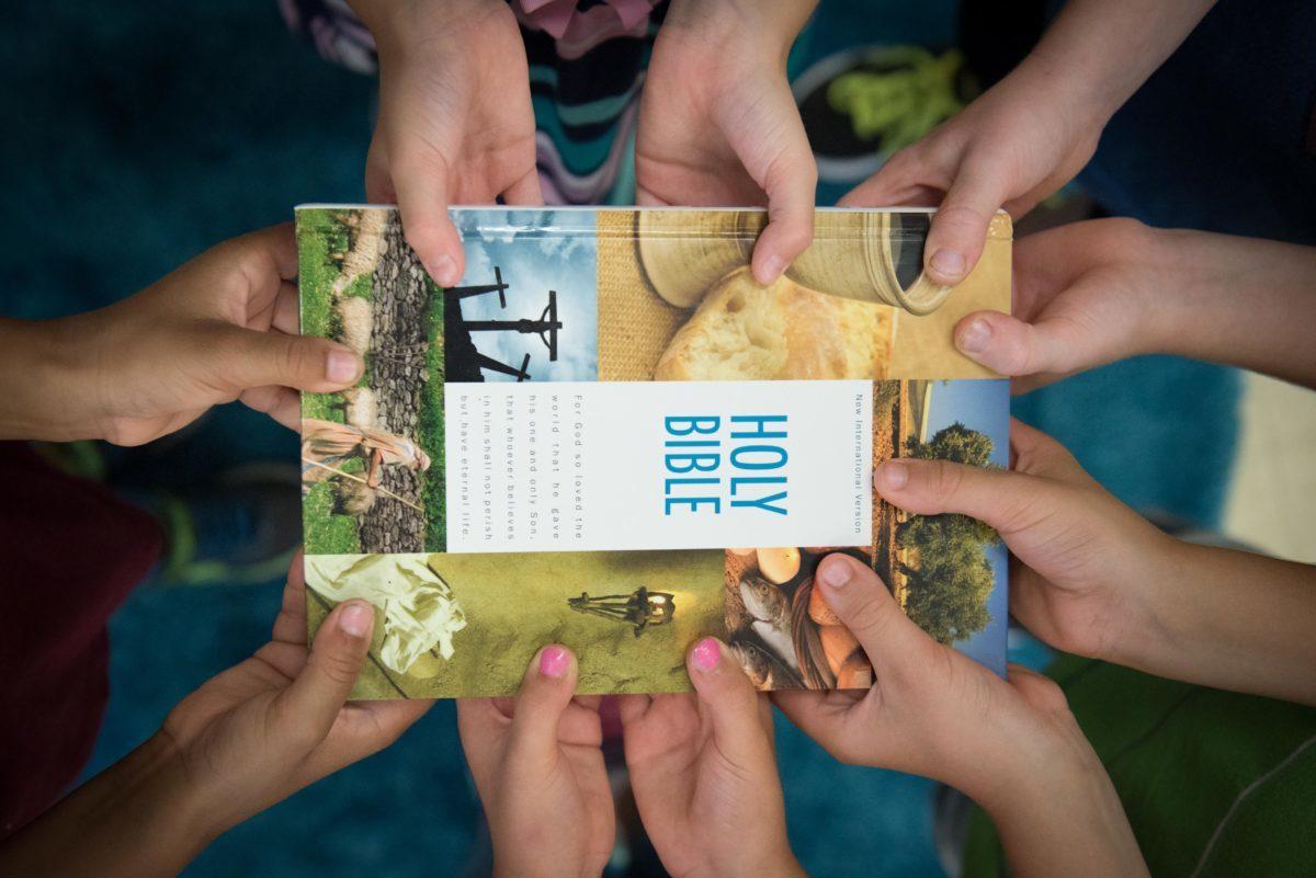 Christian Activities - Children's hands holding a Bible.