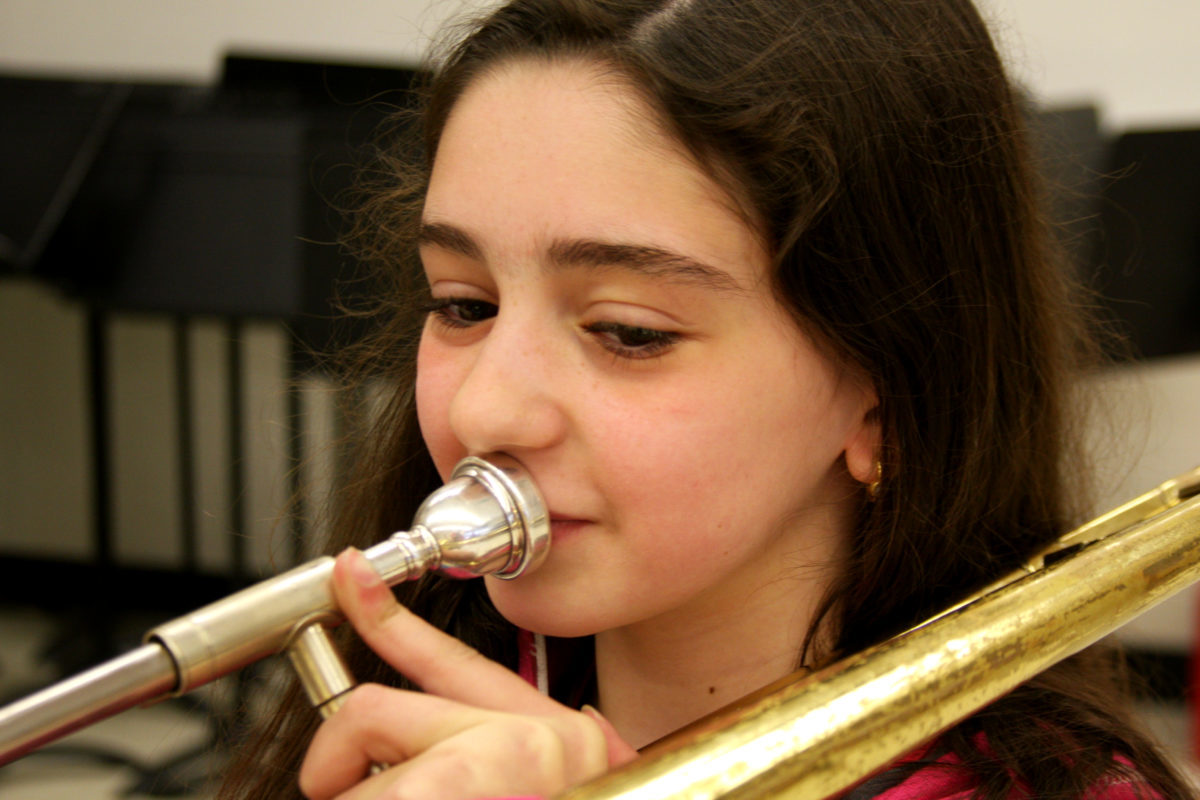Photo of girl playing music on a trombone.